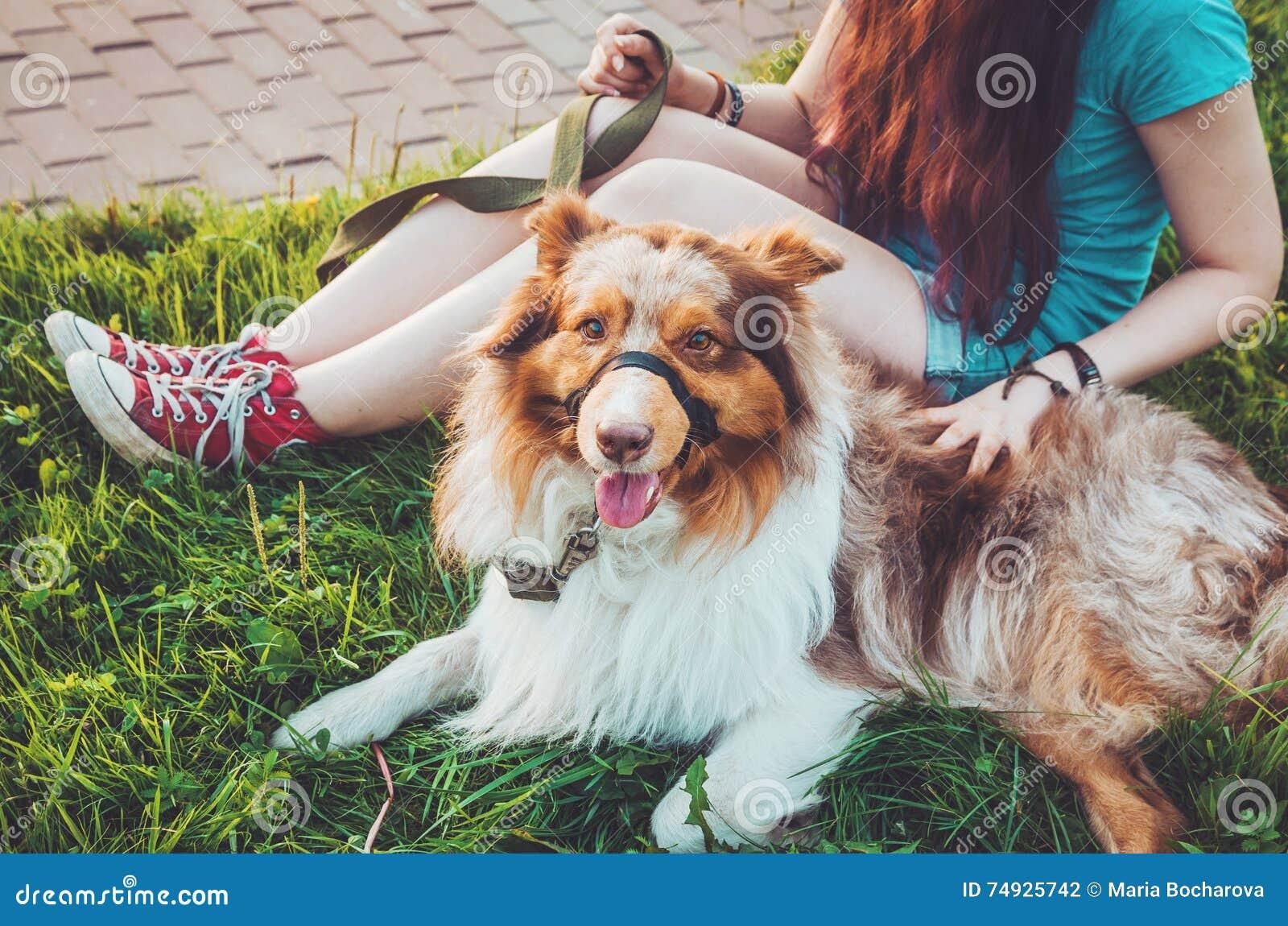 La testarossa sveglia pets il rilassamento sull erba verde dopo gioco lungo, ha un divertimento all aperto Giovane ragazza felice