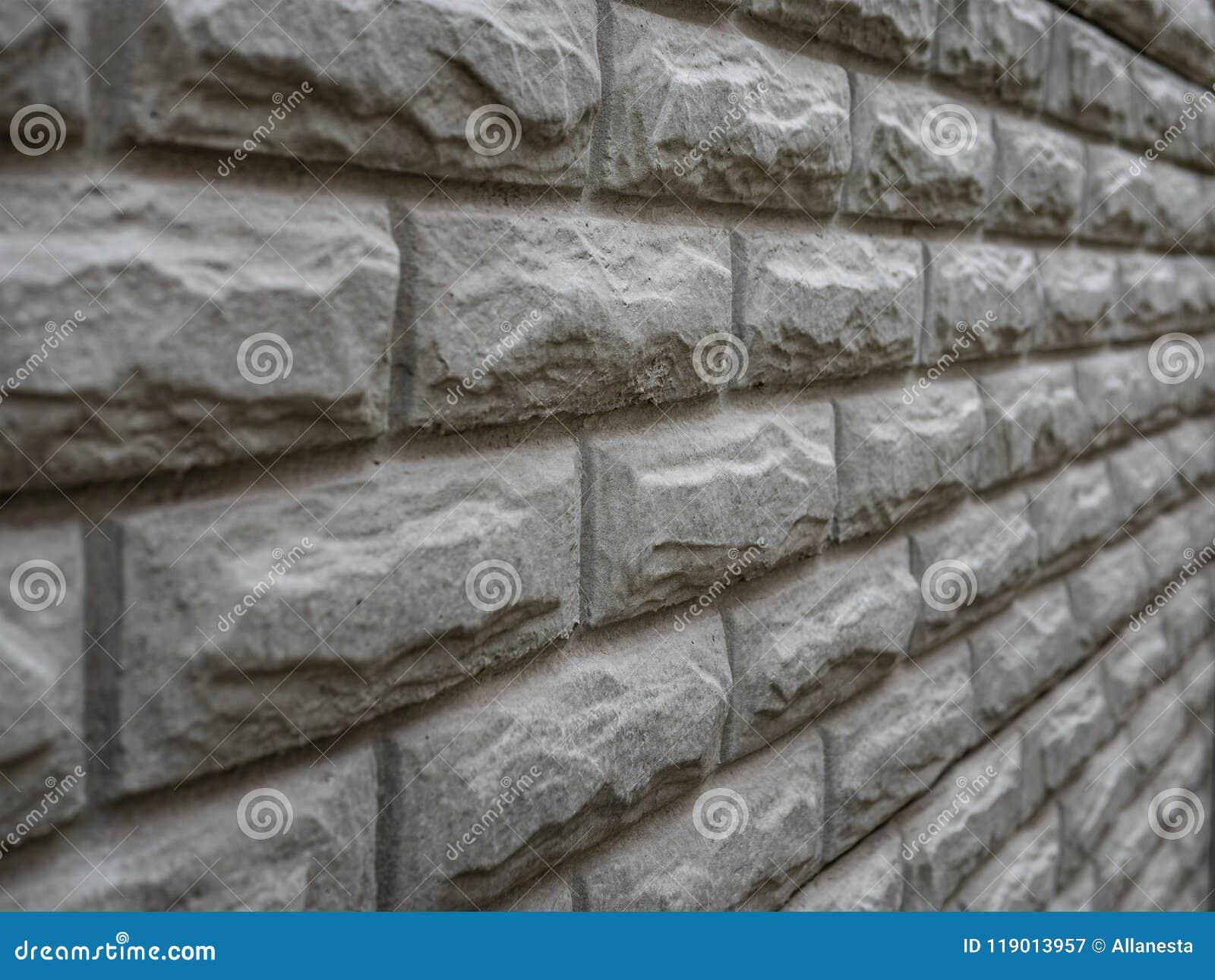 La textura resistida extracto manchó el estuco viejo gris claro y envejeció el fondo blanco de la pared de ladrillo de la pintura