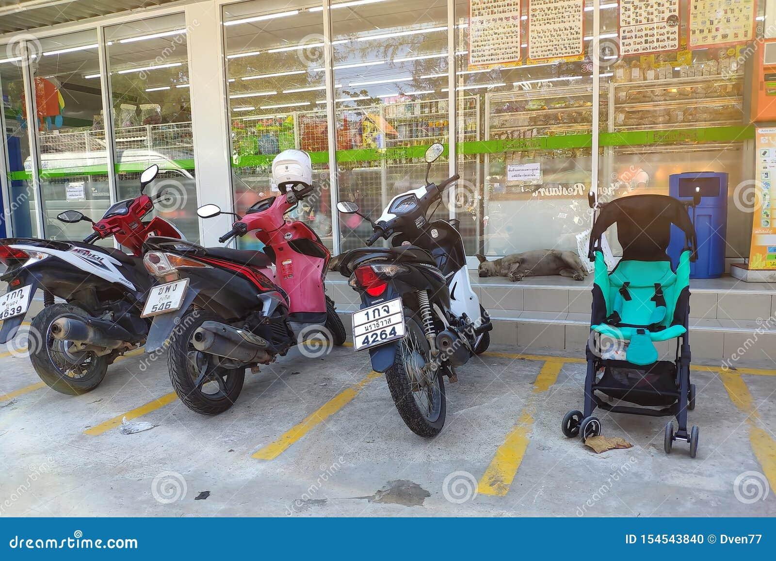 La Thaïlande, Phuket - 23 février 2019 : Stationnement de moto et une poussette de bébé dans un parking devant le magasin Tours d