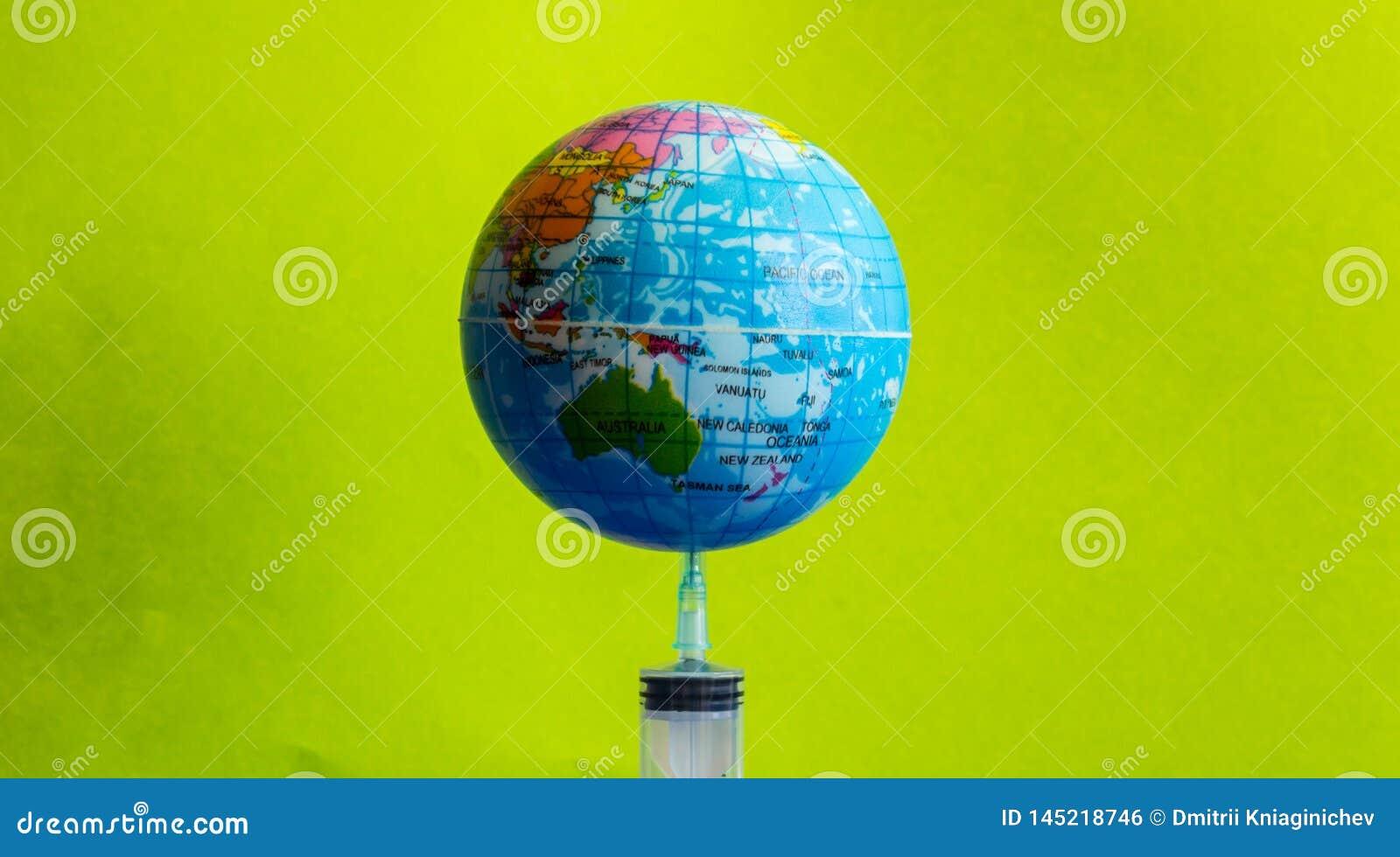 La tierra modelo en la jeringuilla con el fondo verde - imagen