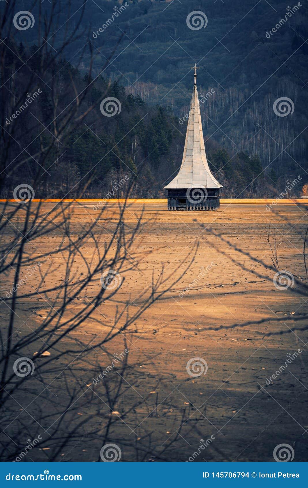 La torre di una chiesa situata in un villaggio sommerso da spreco sterile da una società di estrazione mineraria in un posto dram
