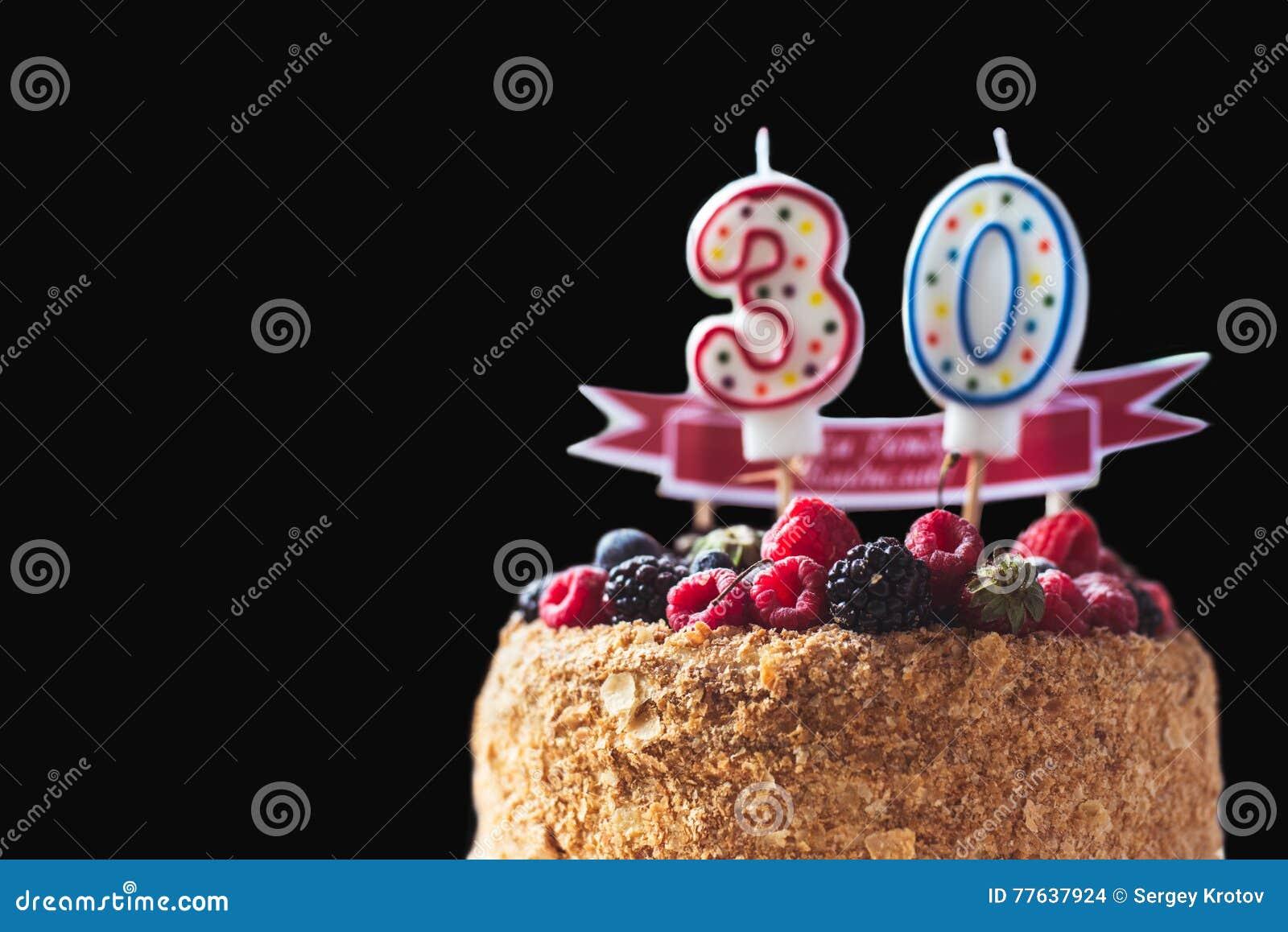 La torta de cumpleaños de la zarzamora de las frambuesas con las velas numera 30 en fondo y copyspace negros para su texto