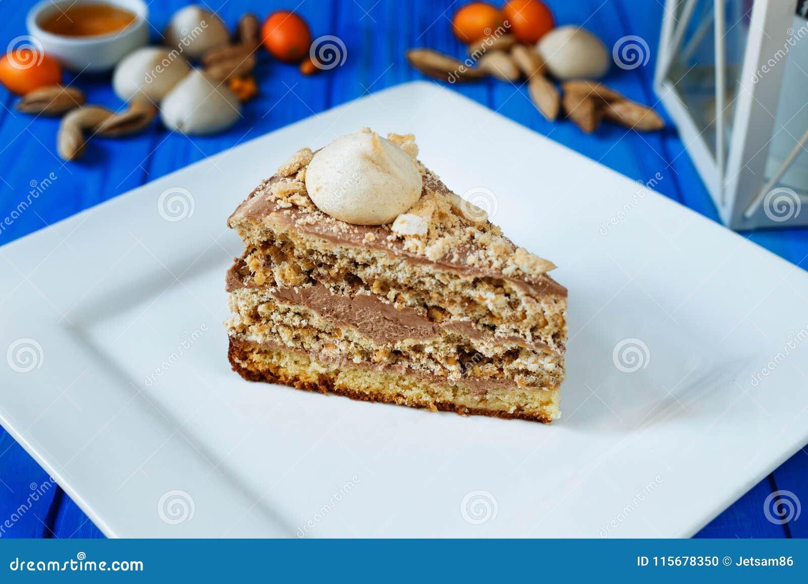 La torta del merengue con las avellanas y el caramelo untan con mantequilla la crema