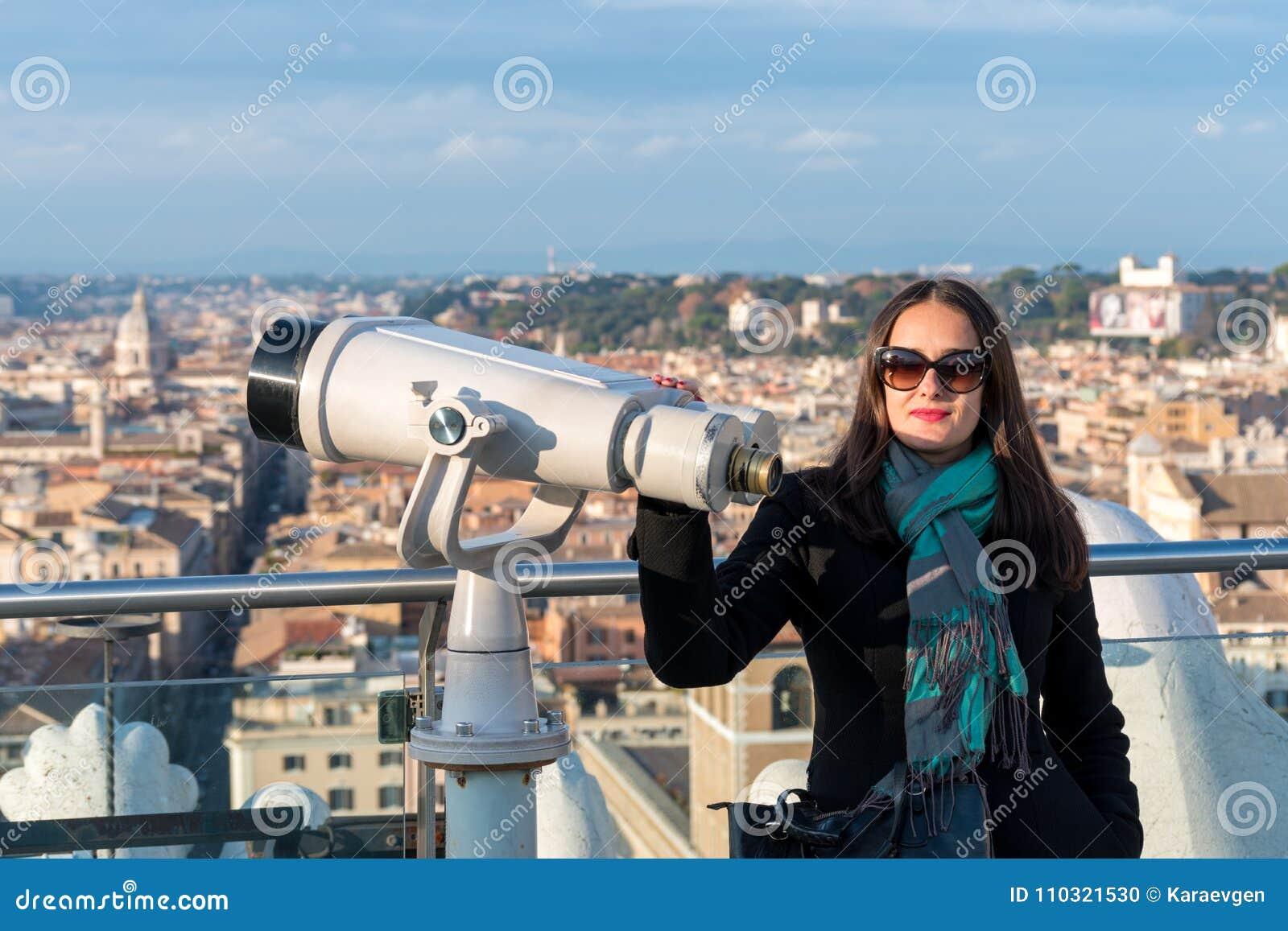 La touriste de femme presque se tient aux jumelles sur la ville Rome