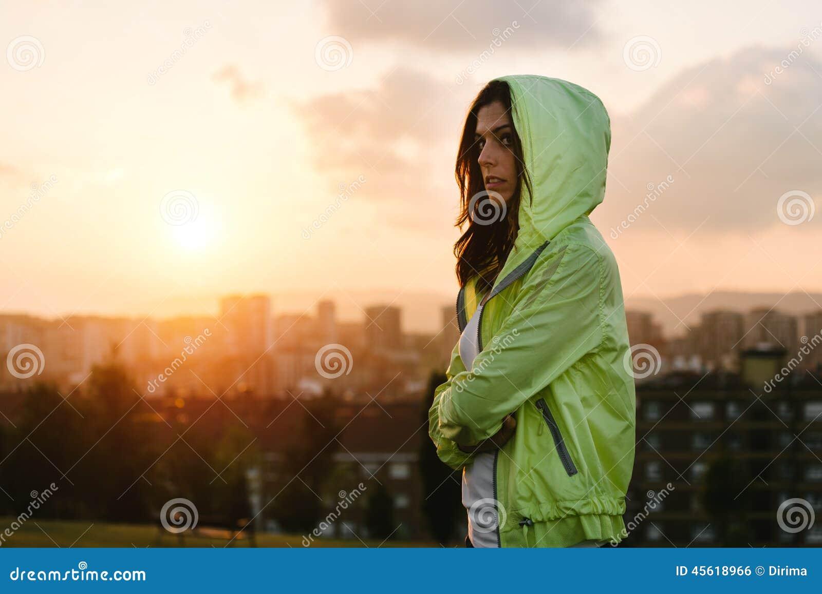 La travesía urbana del atleta de sexo femenino arma en puesta del sol y fondo de la ciudad