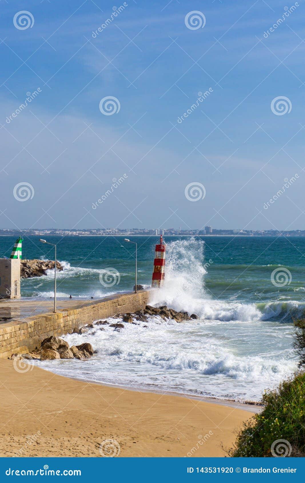 La vague éclabousse contre le phare à Lagos, Portugal