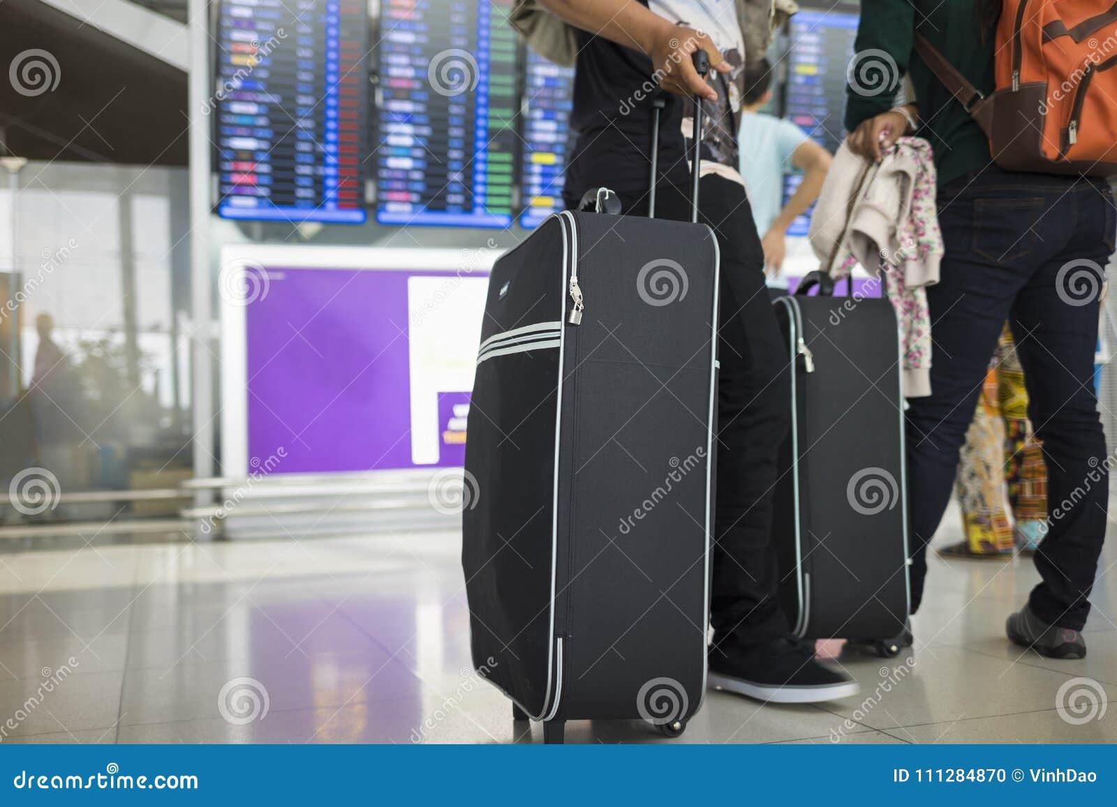 La valigia di viaggio contro informazioni di volo imbarca su fondo Concetto del viaggio in aeroplano