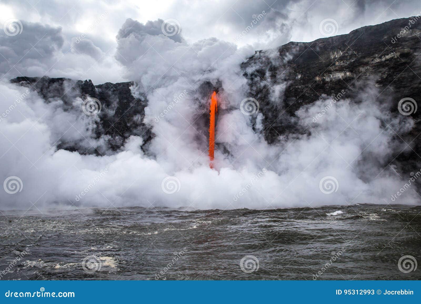 La vapeur éclate de l océan froid pendant que la lave chaude se renverse dans l eau