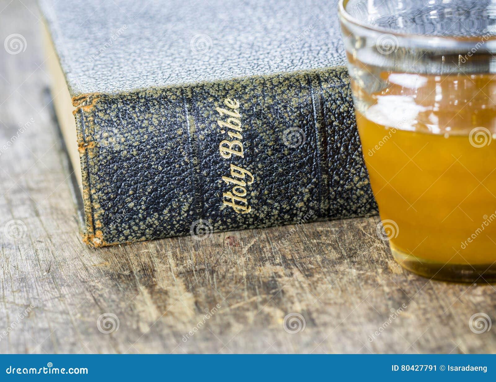 Credenza Con Tazze : La vecchia bibbia santa con una tazza di miele immagine stock