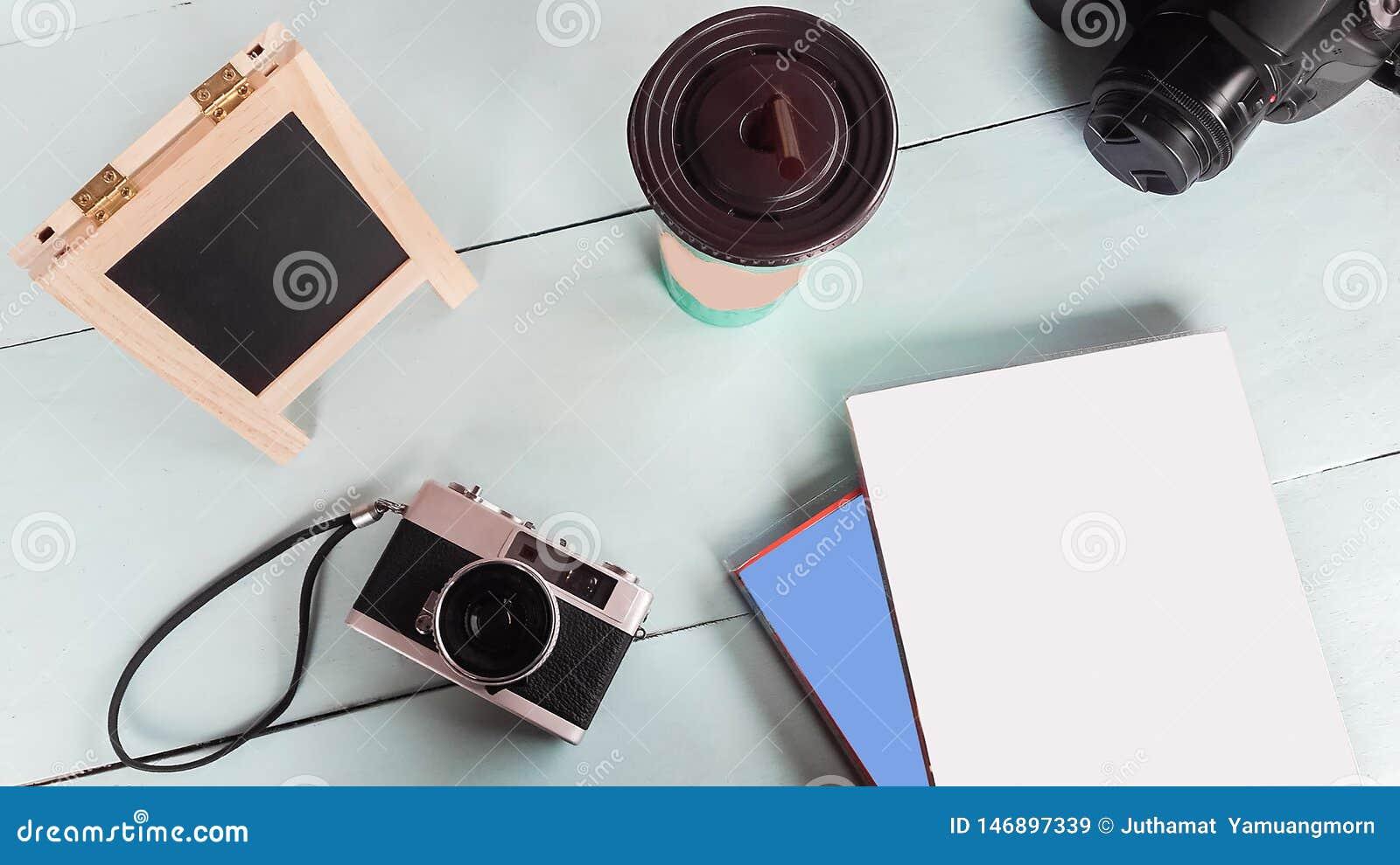 La vecchia macchina da presa con il taccuino, la scrittura del bordo, la carta ed il tavolino da salotto sul legno verde