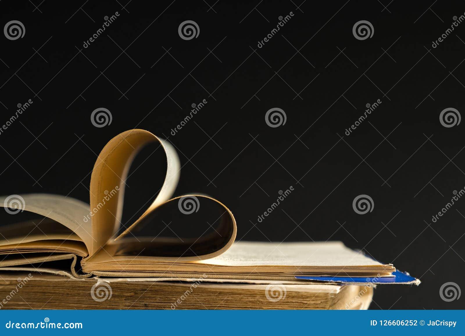 La vecchia pagina del libro della copertina rigida decora a forma del cuore per amore in val