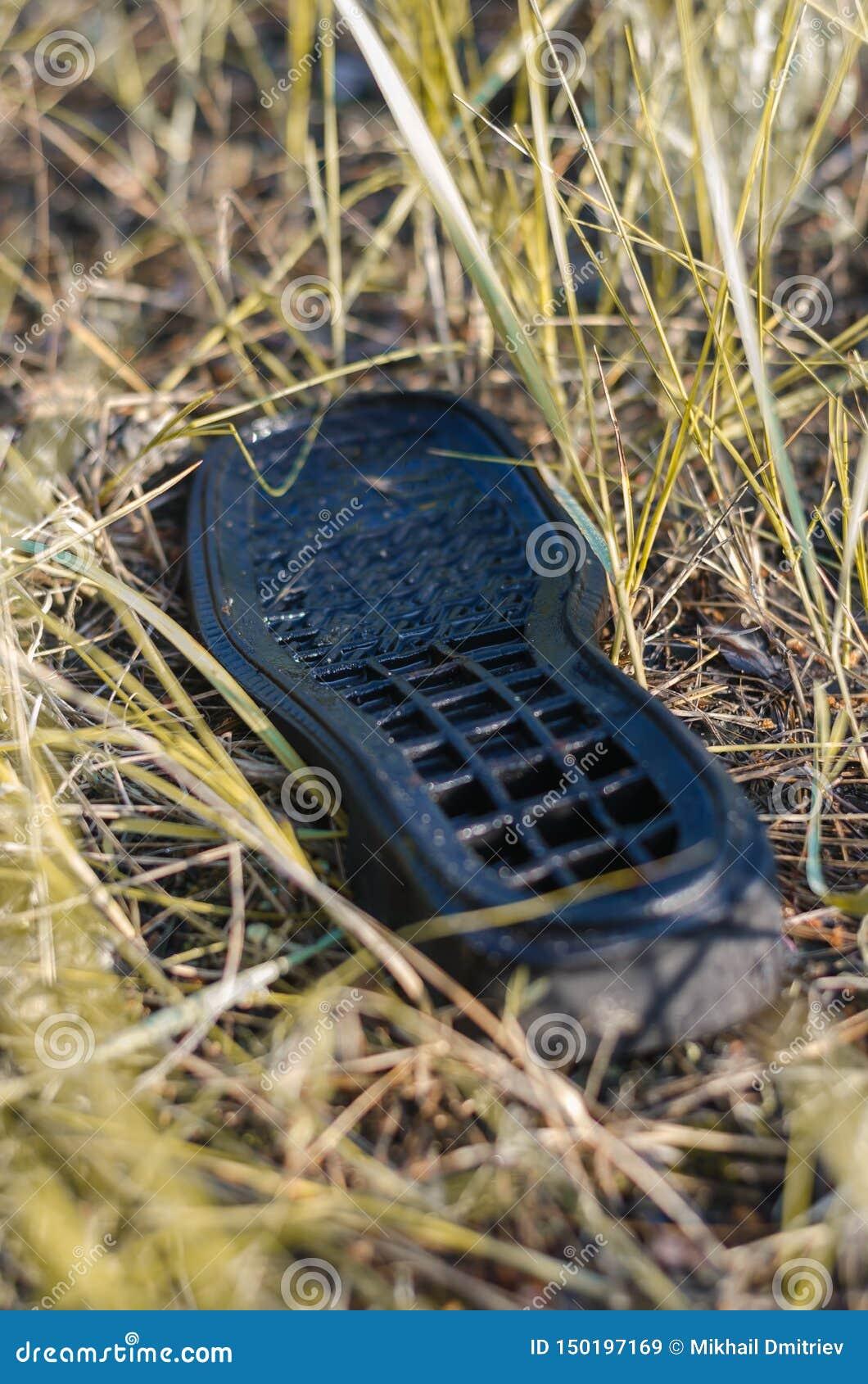 La vecchia scarpa sola si trova sulla terra Bagni dalla pioggia Fuoco molle