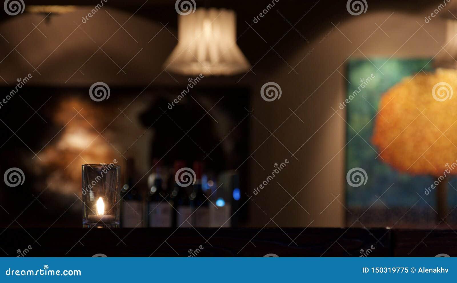 La vela se coloca en la tabla en la luz sorda en el restaurante