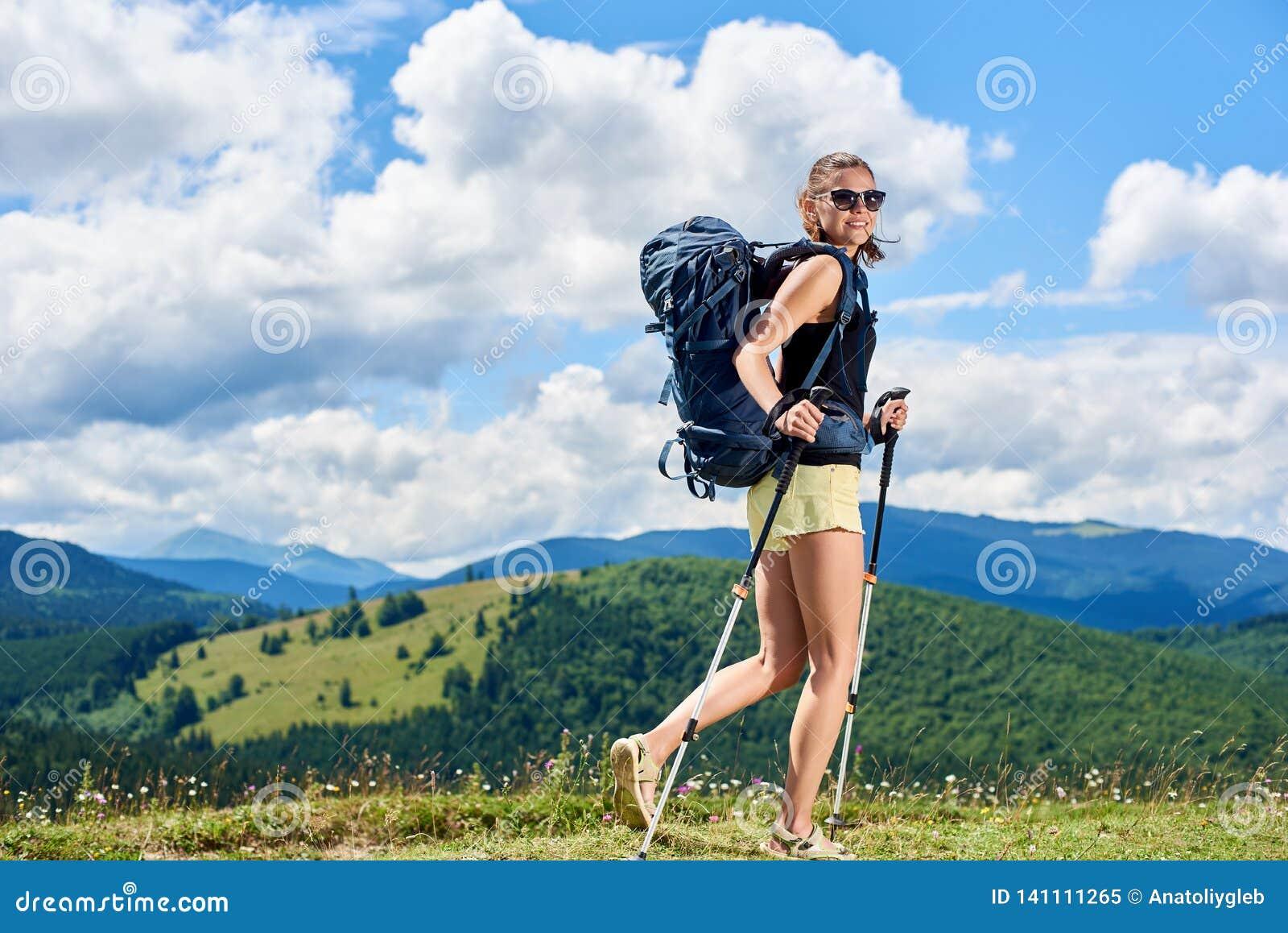 La viandante della donna che fa un escursione sulla collina erbosa, zaino d uso, facendo uso del trekking attacca nelle montagne