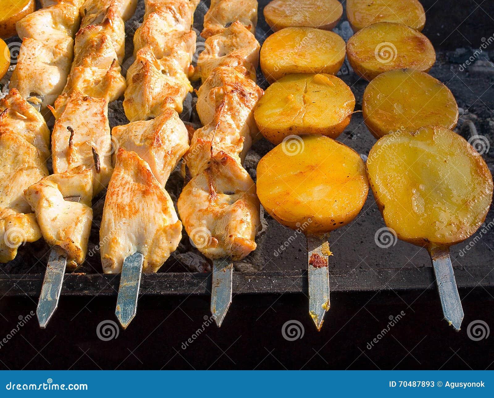 La viande et les pommes de terre frites délicieuses appétissantes sur un barbecue grillent dehors