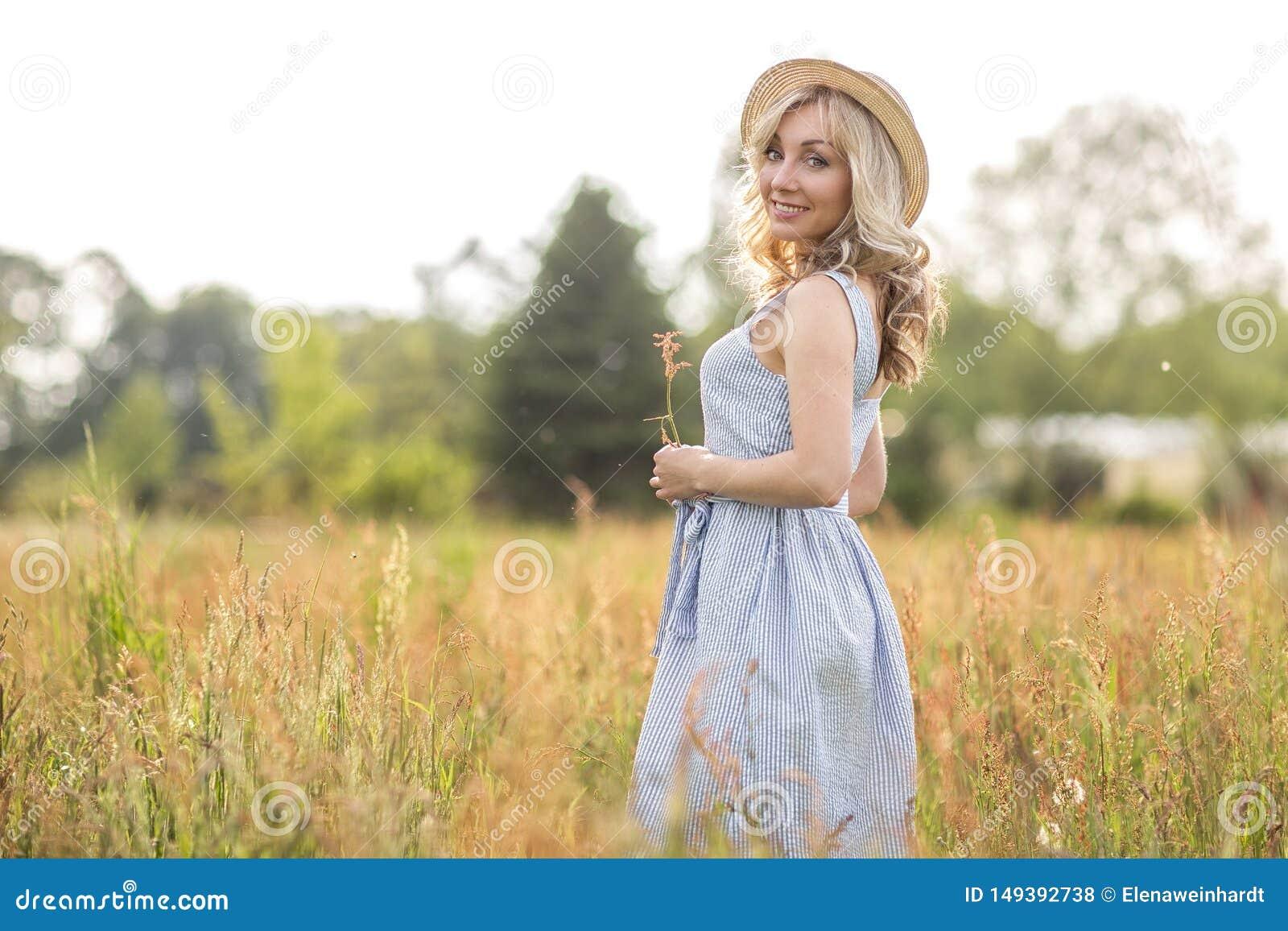 La vie rurale et rurale Marche par la jeune femme blonde de pr? dans un chapeau ?t?