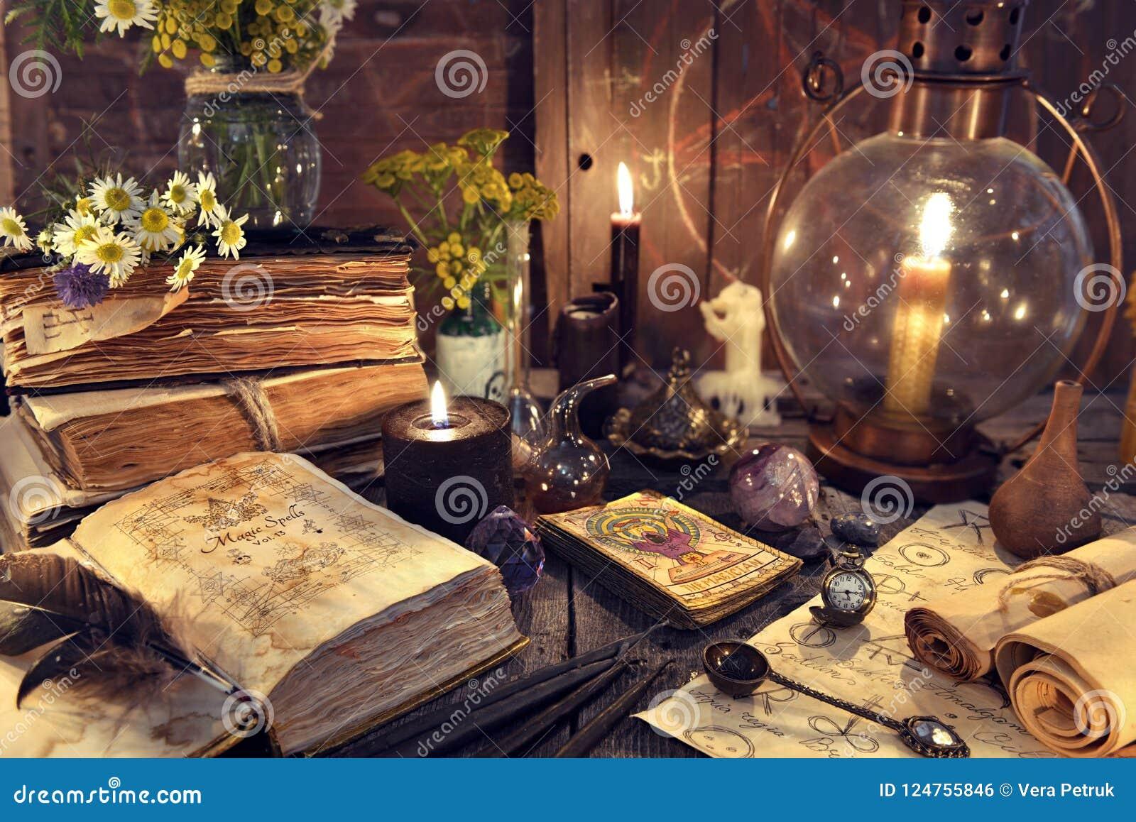 La vie toujours avec la lampe démodée, les livres magiques de sorcière, les cartes de tarot et les vieux papiers