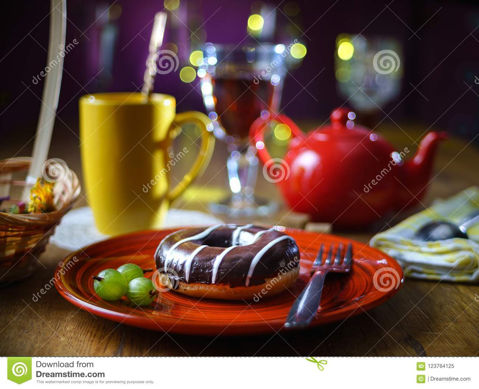 La vie toujours avec un beignet de chocolat d un plat fait main rouge, baies de groseille à maquereau, à l arrière-plan par tasse