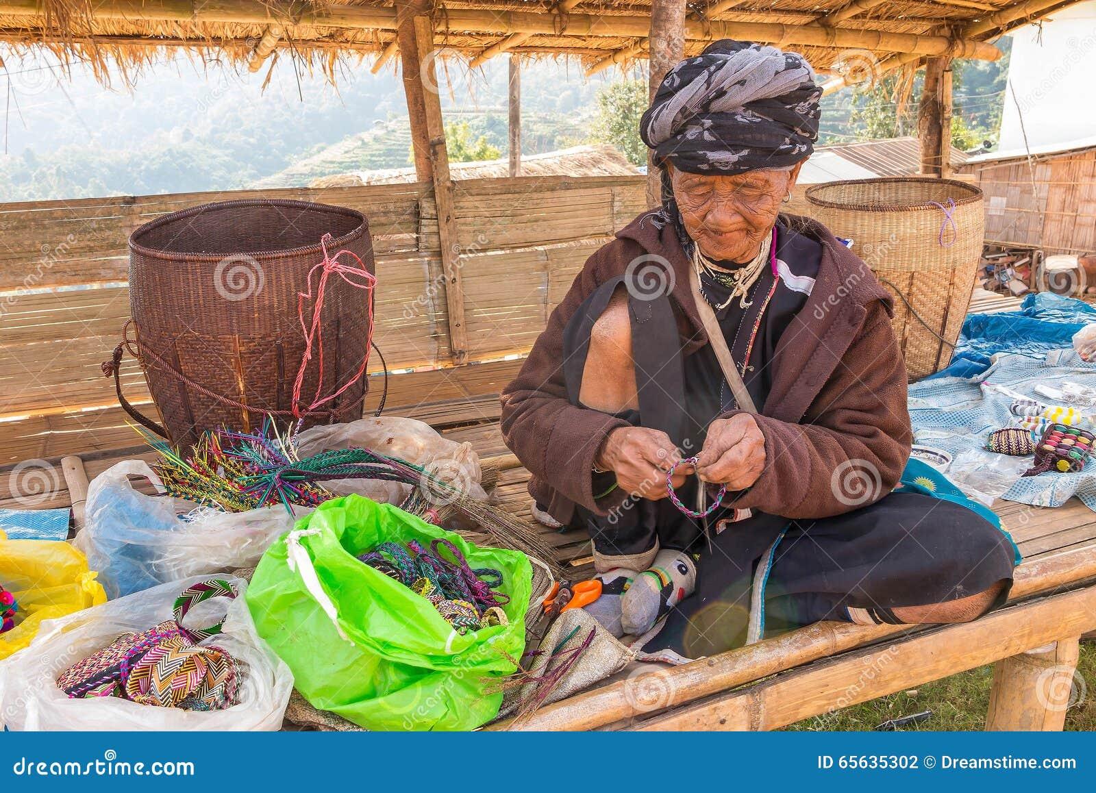 La vieille femme de tribu de colline font un bracelet de travail manuel