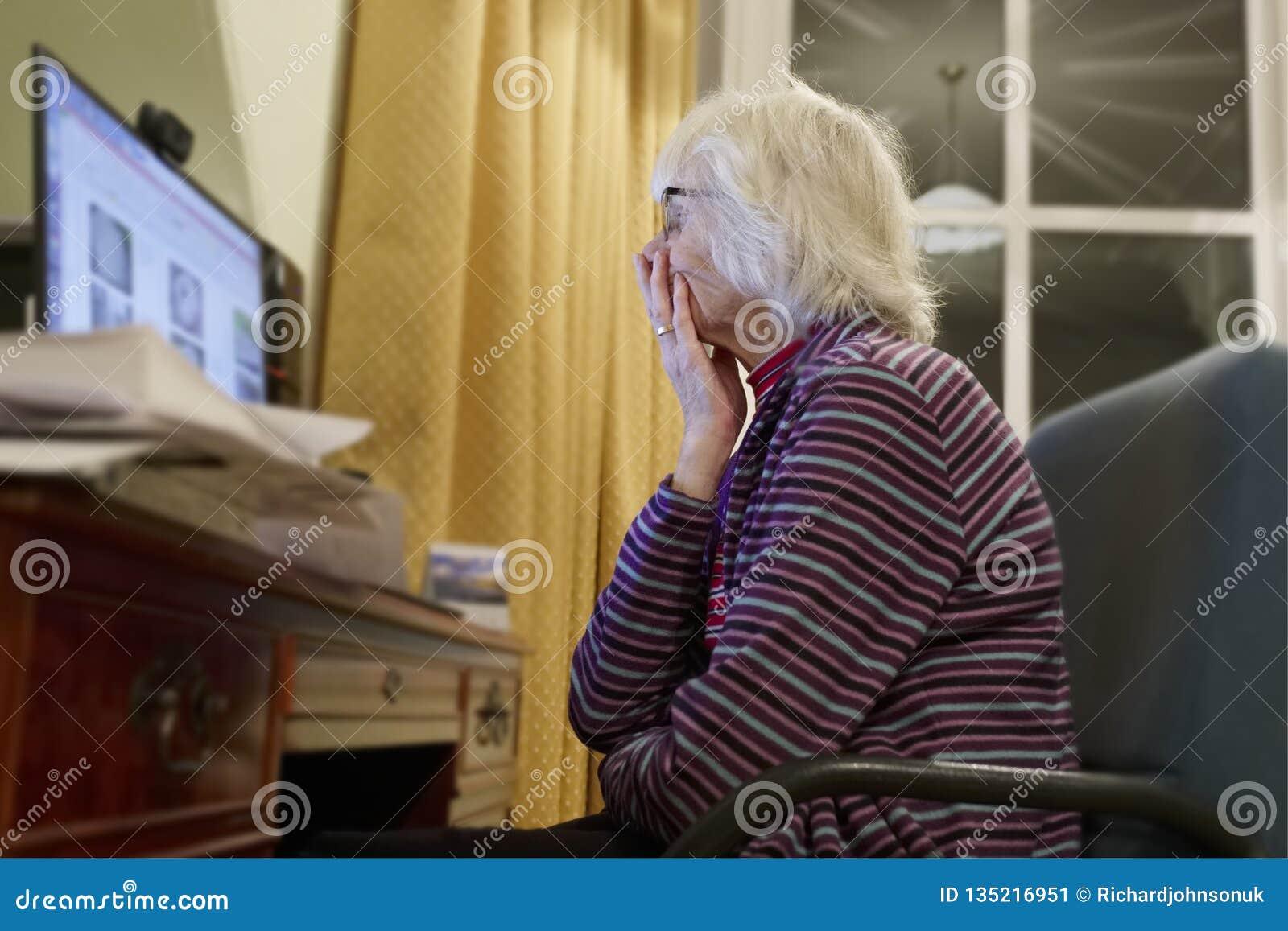La vieja persona mayor mayor que aprende el ordenador y las habilidades en línea de Internet se guardan de Spam del timo del frau