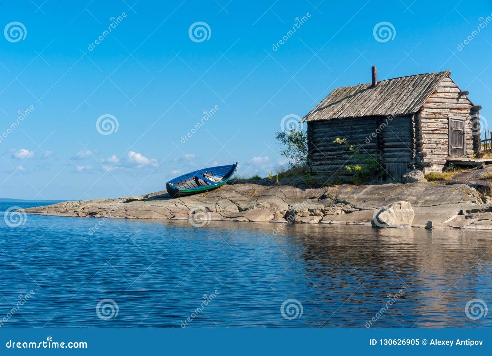 La vieux hutte et bateau en bois sur les lacs rocheux étayent, la Russie