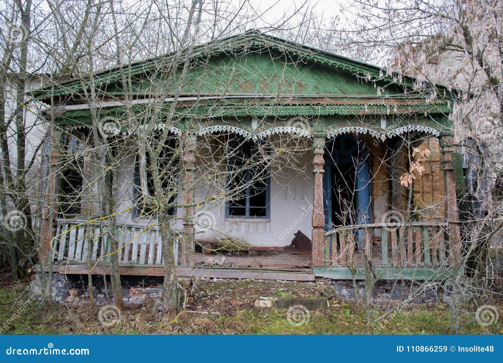 La vieux, négligés, nobles maison et porche parmi les arbres Texture du vieux bois criqué peint vert