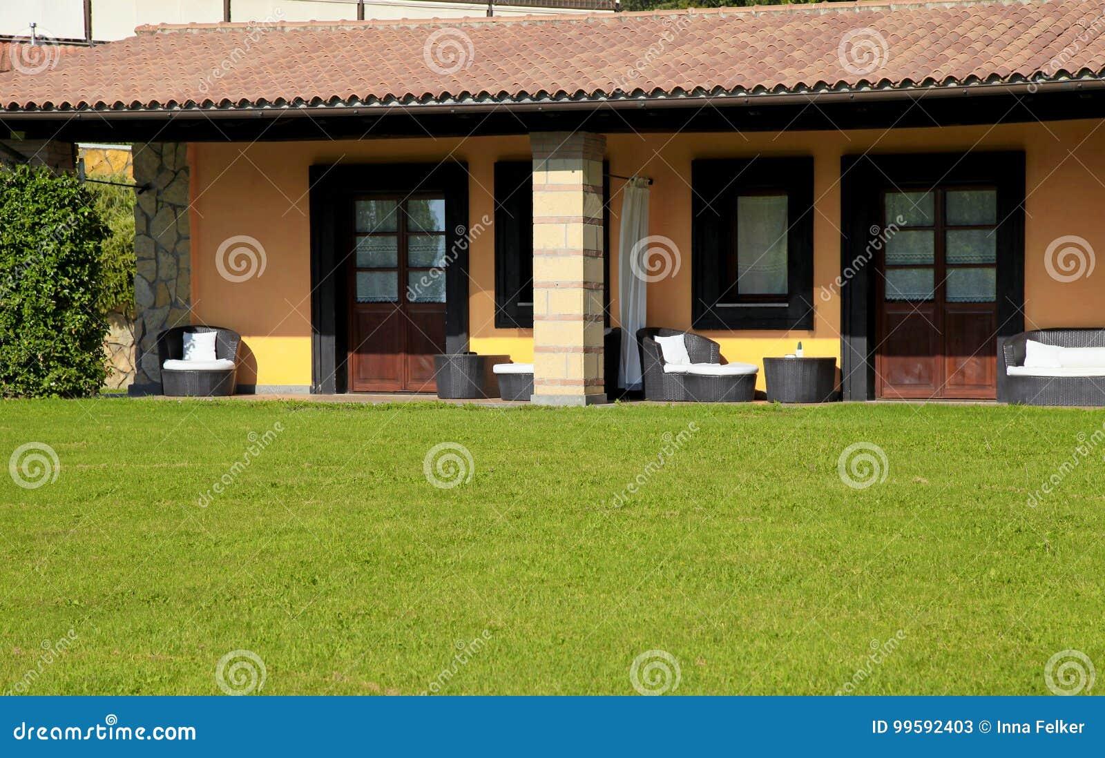 La villa con il terrazzo e lerba verde in villaggio ricorrono l