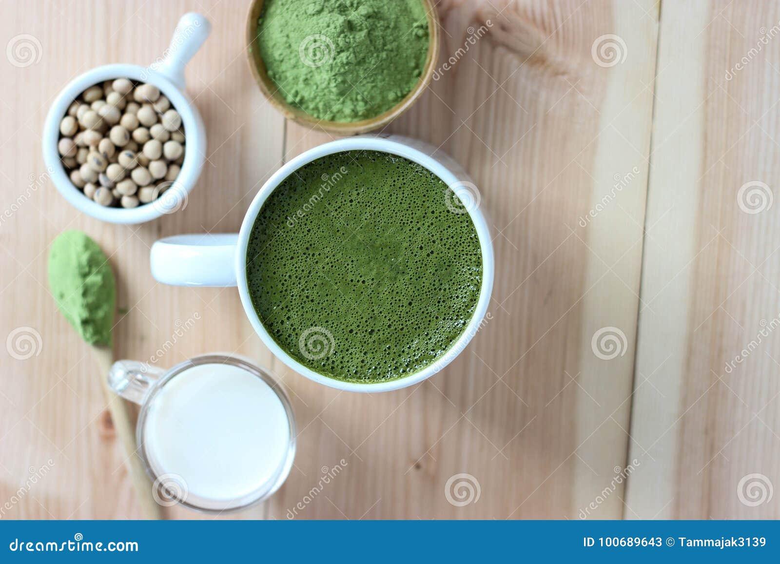 La visión superior, se cierra encima del Latte caliente de Matcha del té verde Adorne con el prisionero de guerra
