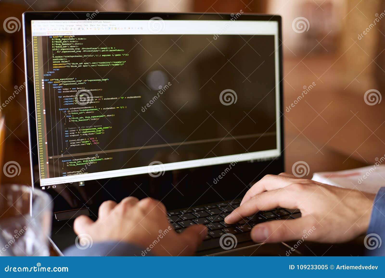 La visión trasera sobre el hombro tiró de programador del desarrollador con el ordenador portátil Código de programa y datos de l