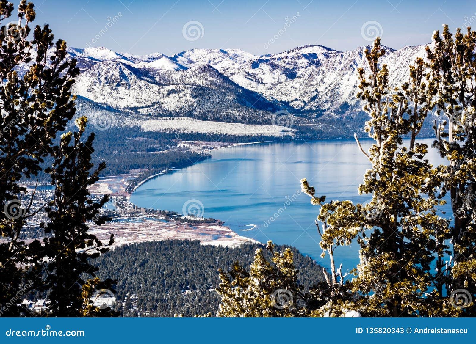La vista aérea del lago Tahoe en un día de invierno soleado, montañas de Sierra cubrió en la nieve visible en el fondo, Californi