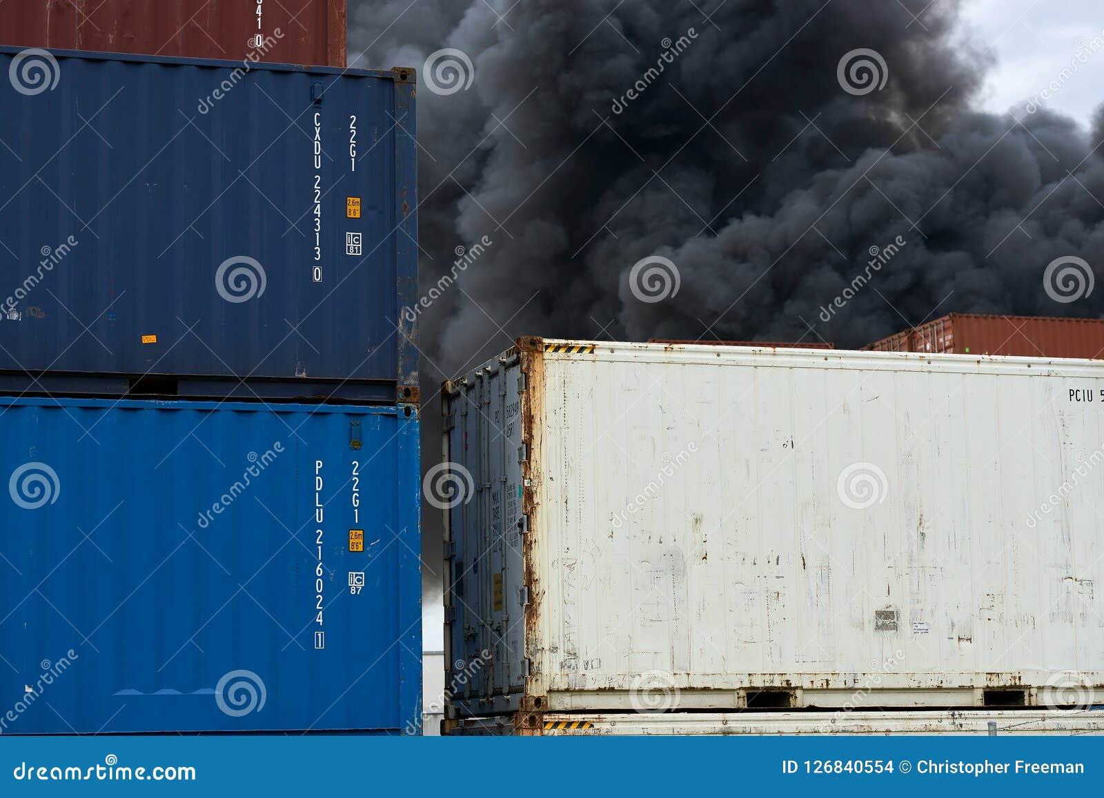La vista abstracta de los contenedores con columnas de humo tóxico de un fuego industrial se alza en el cielo