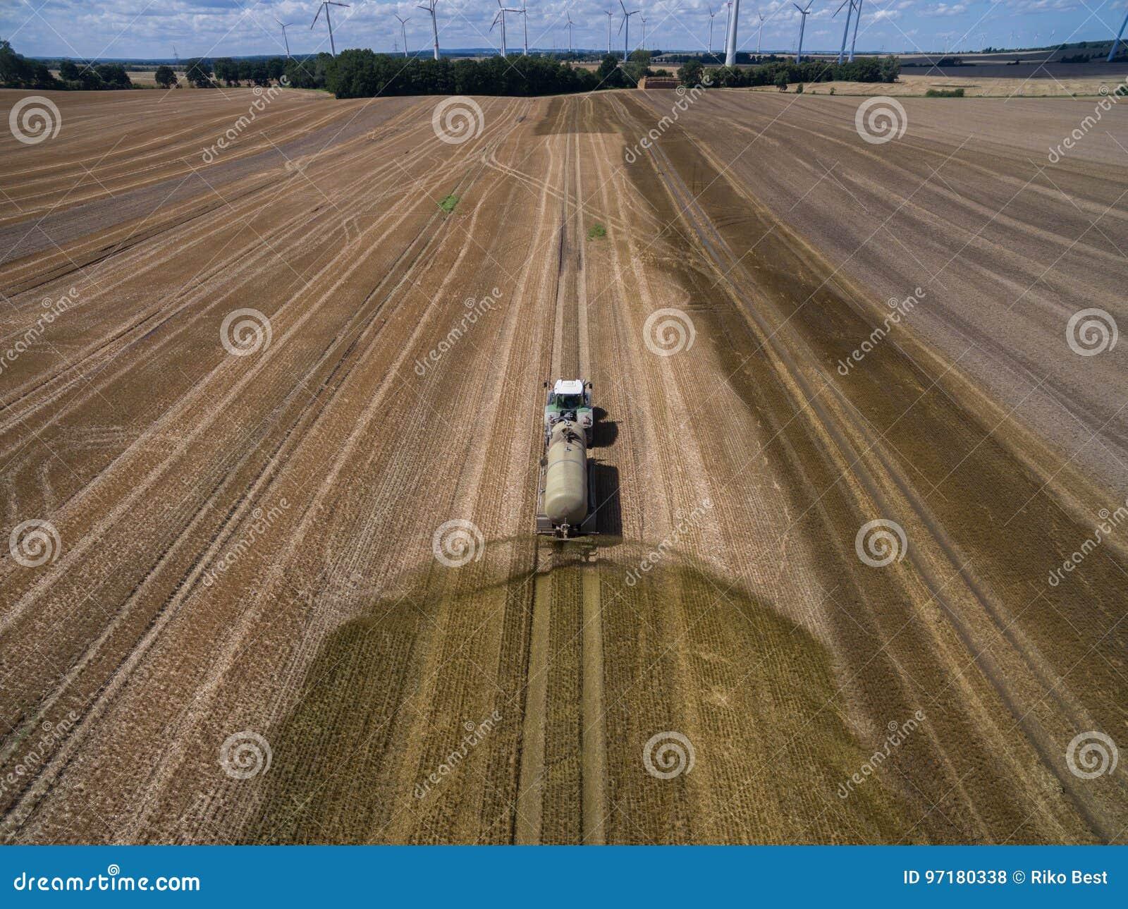 La vista aerea di un trattore agricolo con un rimorchio fertilizza un campo agriculural di recente arato con concime