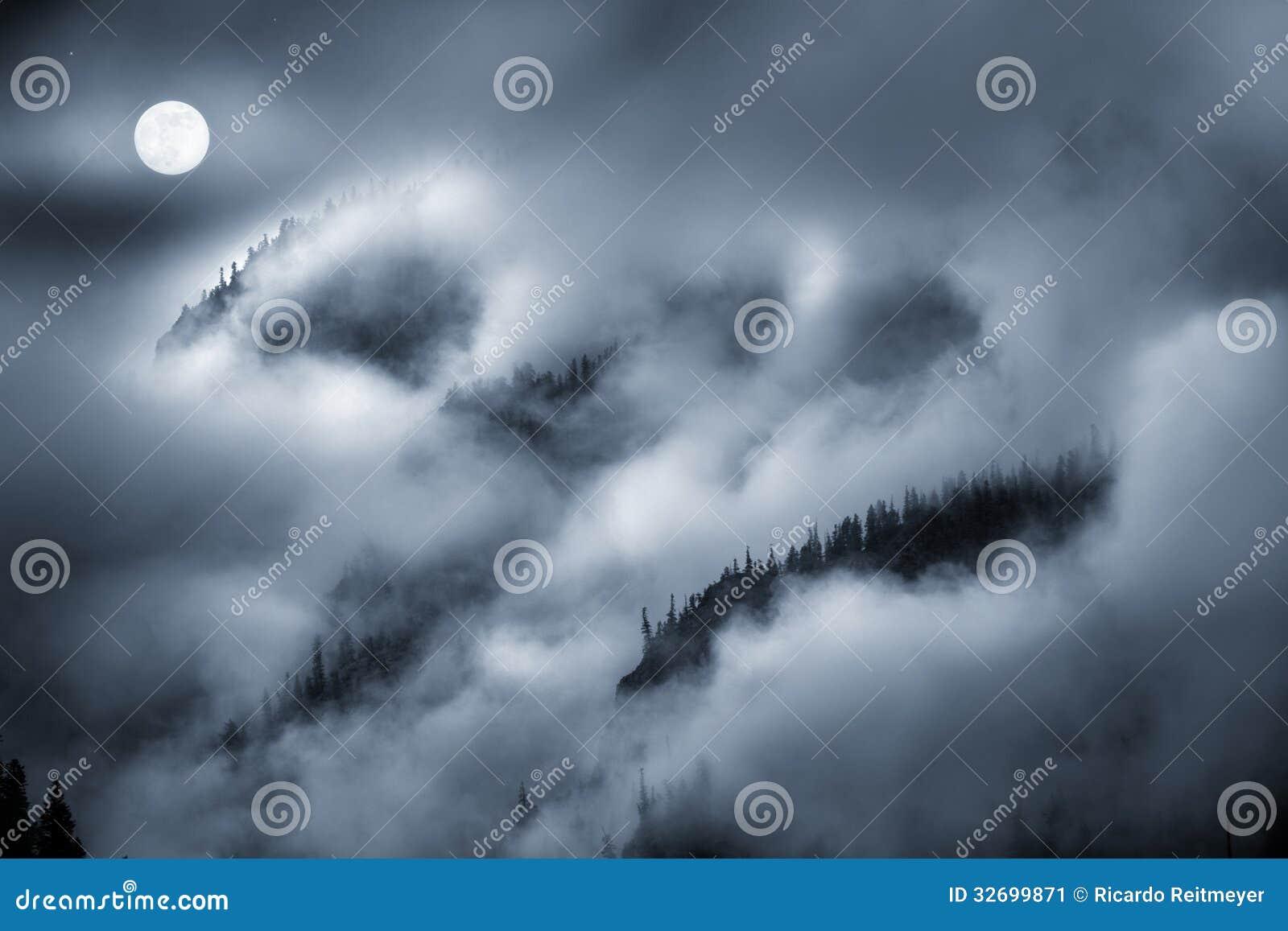 La vista di notte di nebbia ha coperto la montagna accesa dalla luna piena