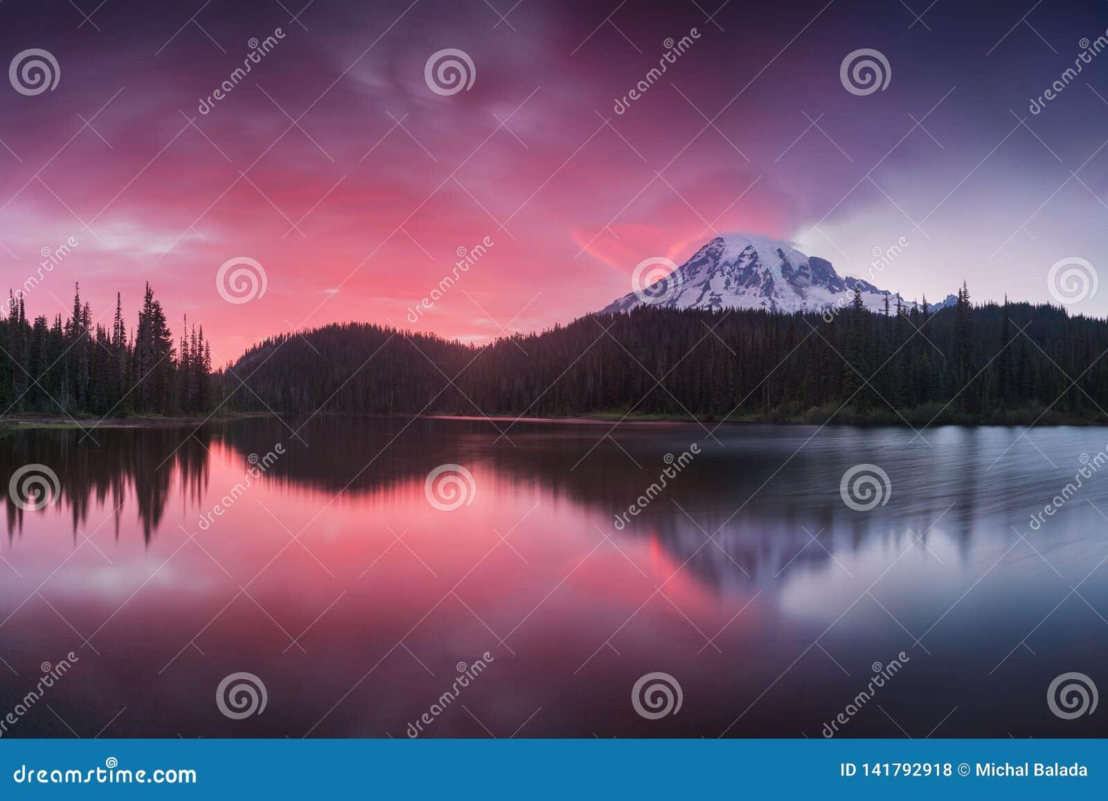 La vista escénica del Monte Rainier reflejó a través de los lagos de la reflexión Luz rosada de la puesta del sol en el Monte Rai