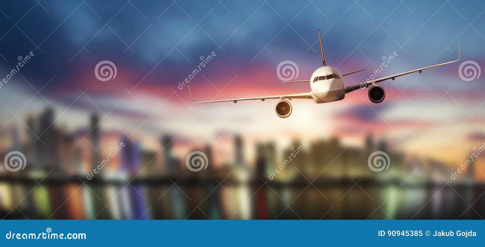 La vista frontale dell aeroplano commerciale, offusca la città moderna su fondo
