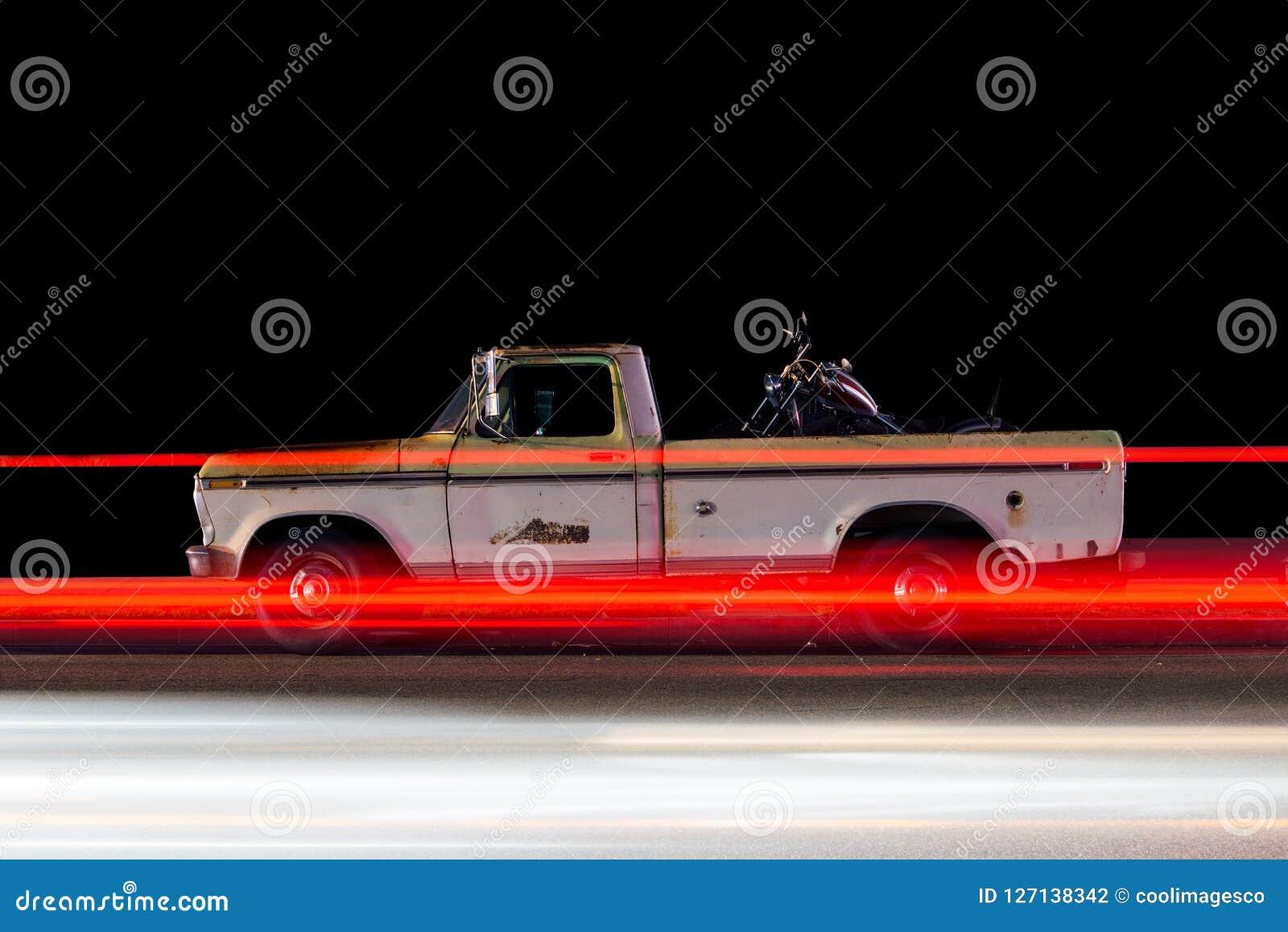 La vista lateral de un vintage clásico coge los rastros del coche y de la luz del camión causados por el tráfico en Venecia, Cali