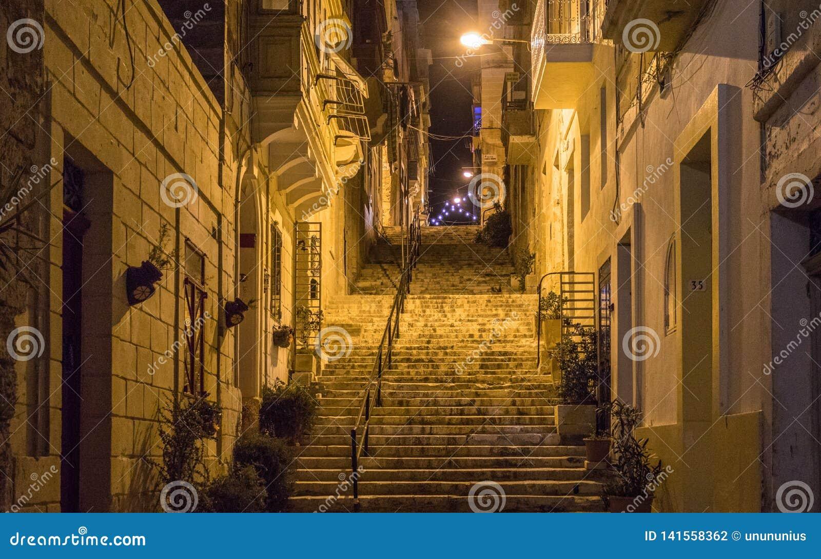 La vista nocturna en un pasillo va arriba, las luces y barandilla cubiertas por los viejos frentes de la casa Algunas flores en e