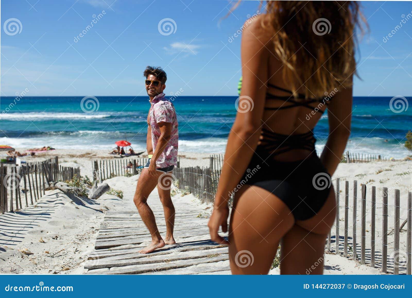 La vista posterior de un hombre joven atractivo sonriente se da vuelta de nuevo a hace conocido con la mujer joven atractiva en l