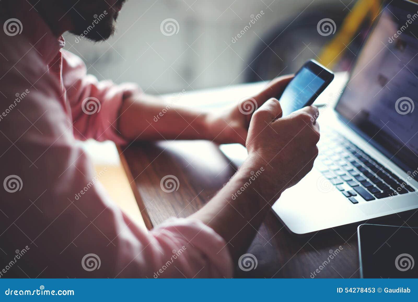 La vista posterior del hombre de negocios da ocupado usando el teléfono celular en el escritorio de oficina