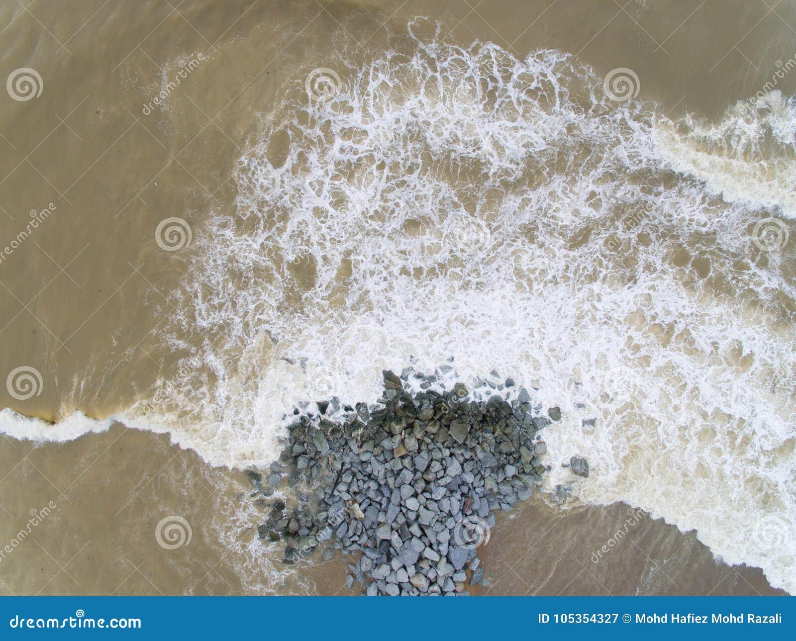 La vista superior aérea del mar agita golpeando rocas en la playa en el cahaya de Pantai bulan
