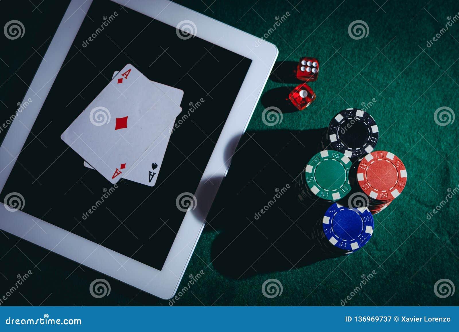 La vista superior de una tabla verde del póker con la tableta, salta y corta en cuadritos Concepto de juego en línea