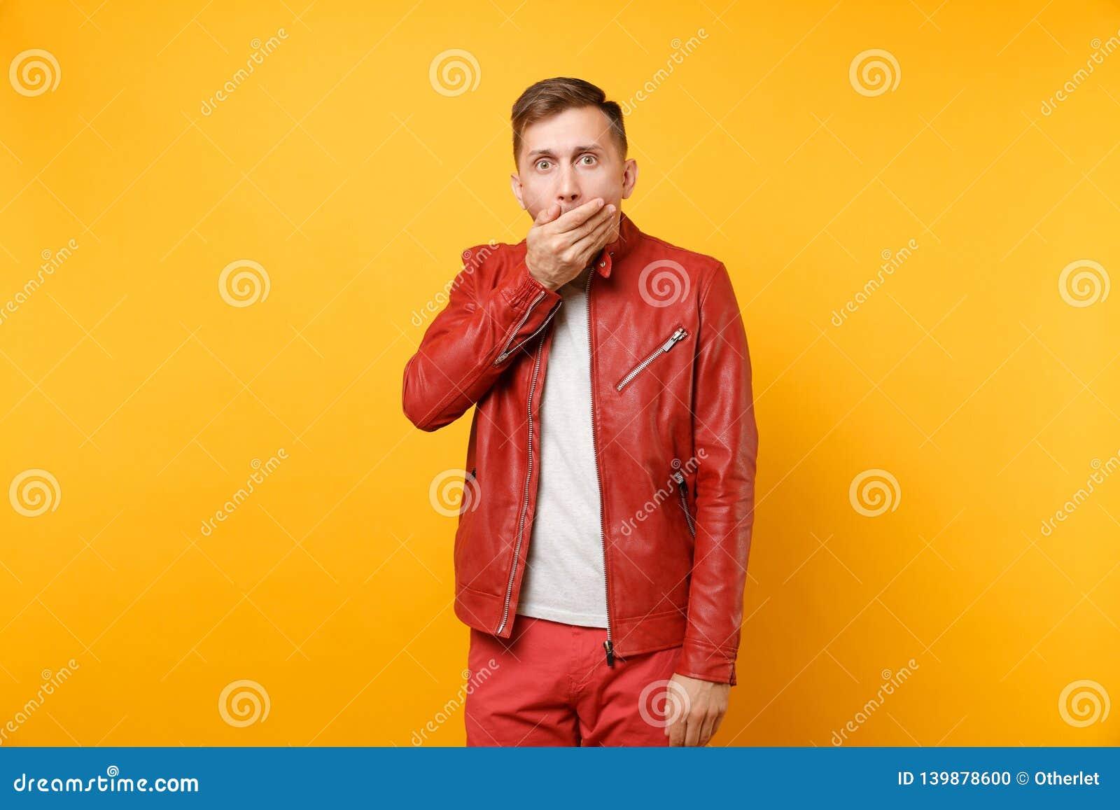 La voga del retrato chocó al hombre joven hermoso 25-30 años en la chaqueta de cuero roja, situación de la camiseta aislada en br