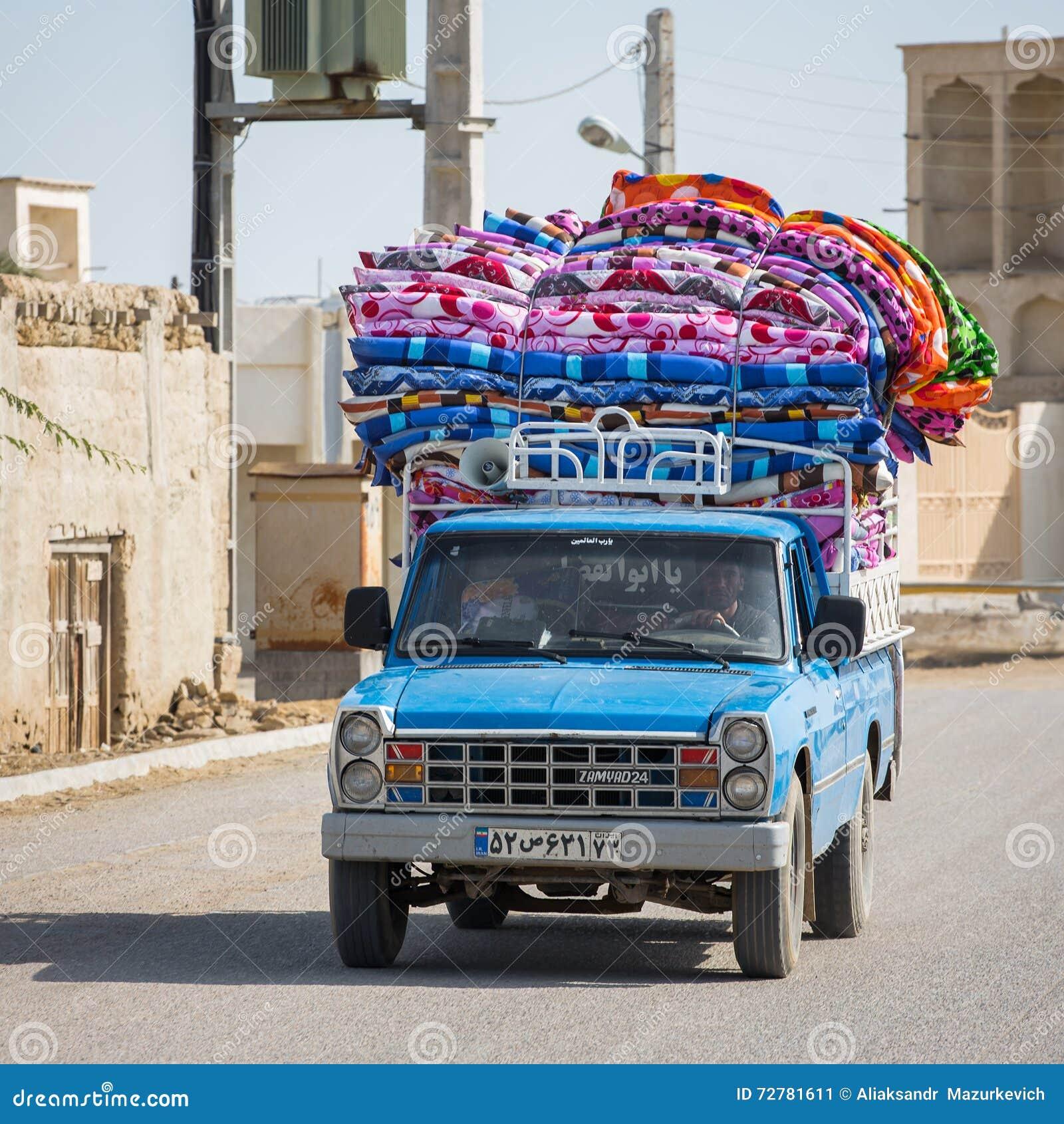 La voiture de collecte chargée avec les matelas colorés monte autour des rues