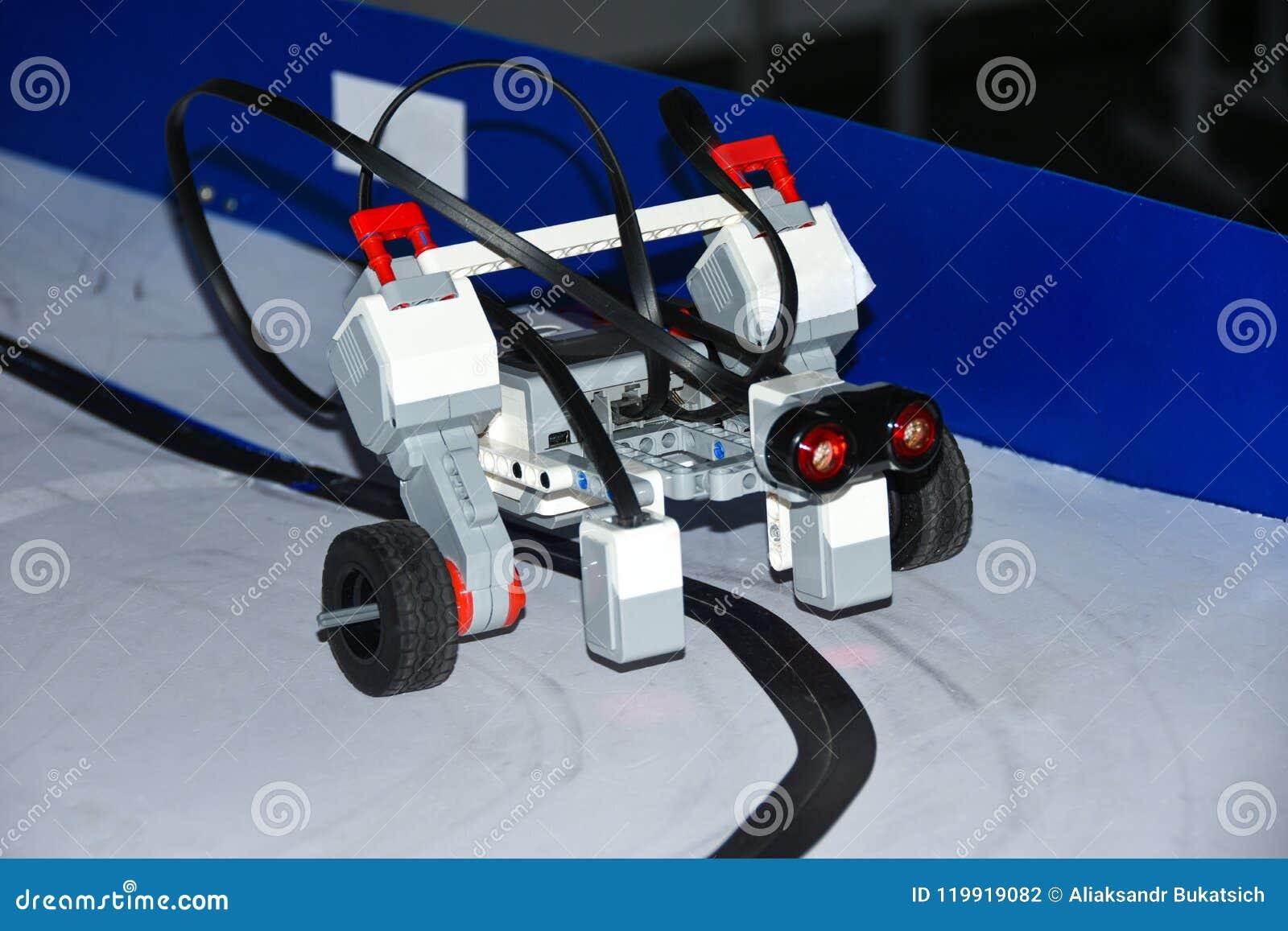 La voiture de robot assemblée à partir des petits groupes de concepteur monte sur la route magnétique par les étudiants de démarr
