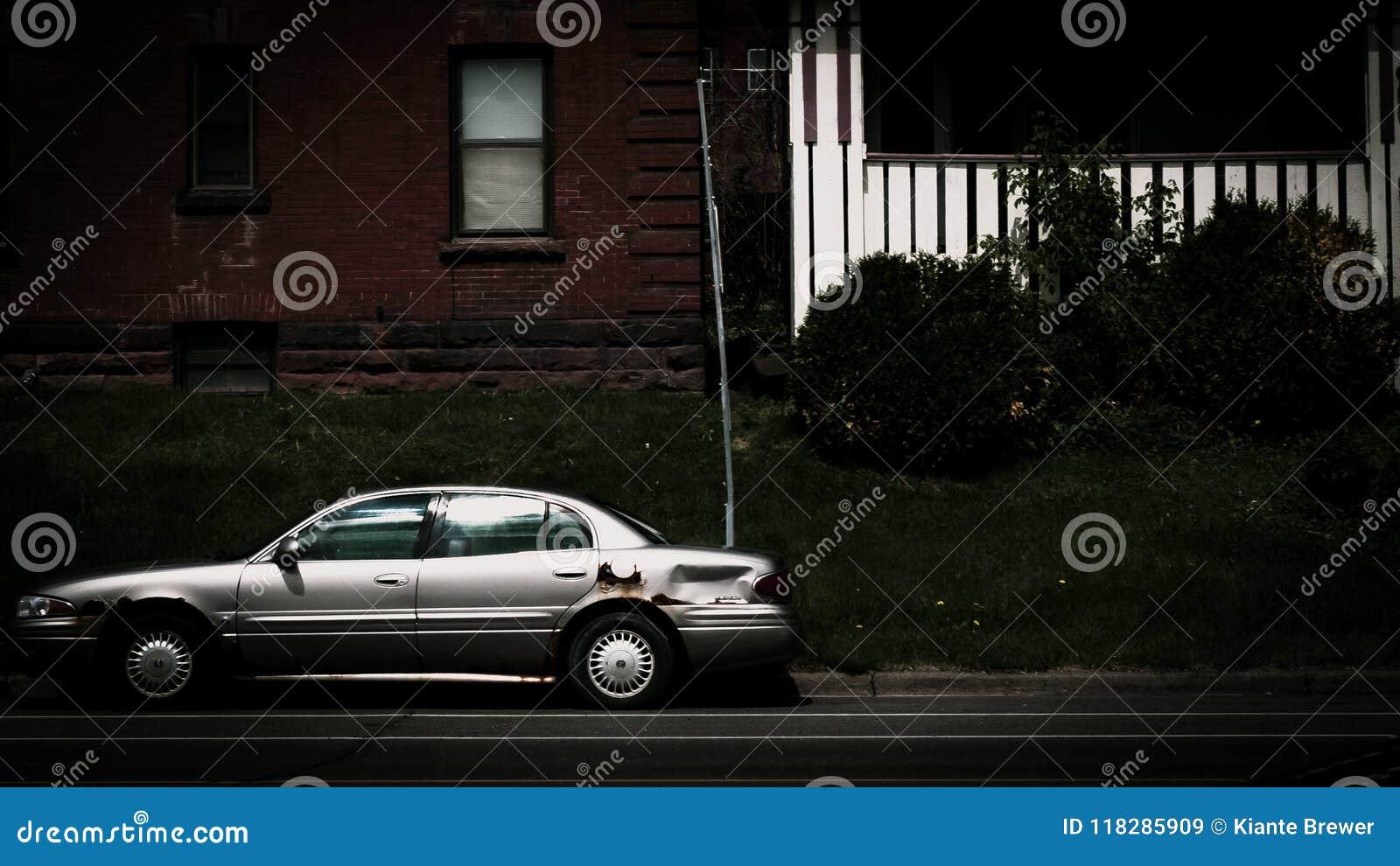 La voiture a garé sur la rue contre deux immeubles