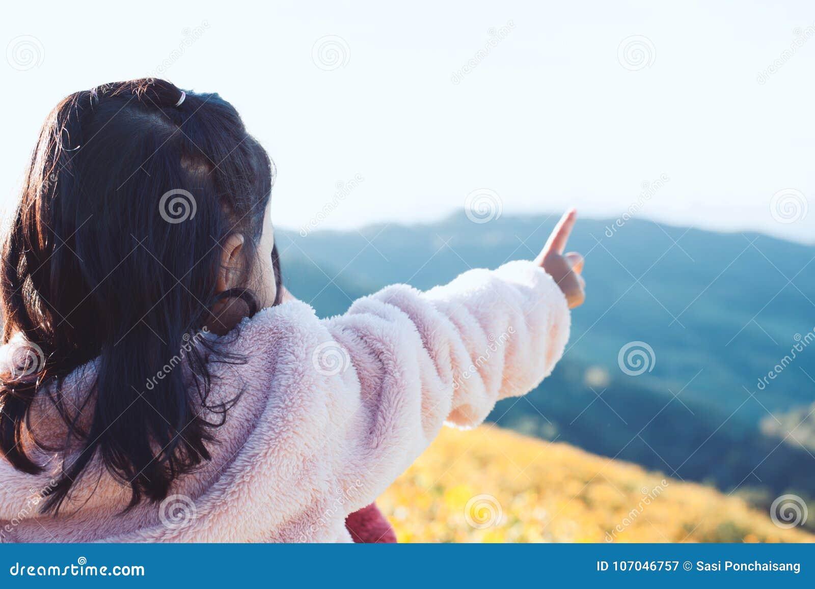 La vue arrière de la petite fille asiatique d enfant a mis dessus le manteau soulèvent son bras