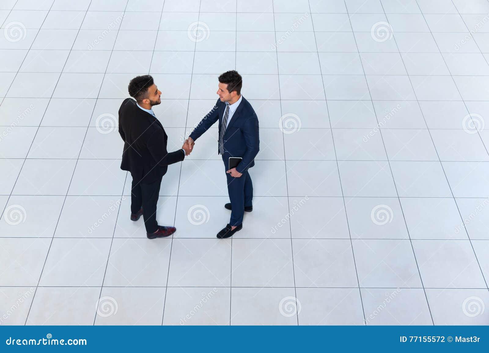 La vue d angle supérieur de geste d accueil de secousse de main d hommes d affaires, deux hommes d affaires font l affaire la poi