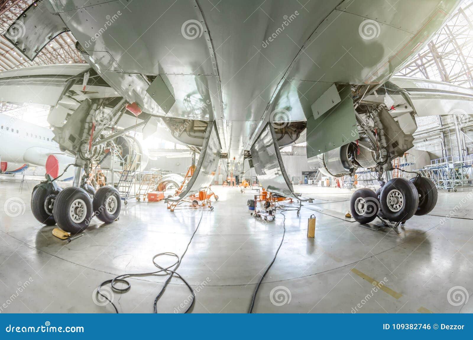 La vue de dessous les avions entre les supports de châssis de roule dedans le hangar
