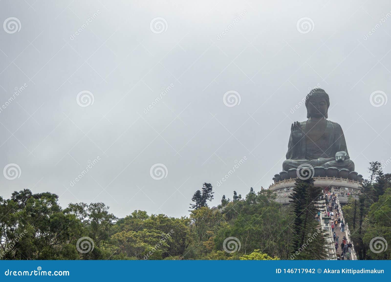La vue de face de Tian bronzent le grand Bouddha sur le fond obscurci de ciel