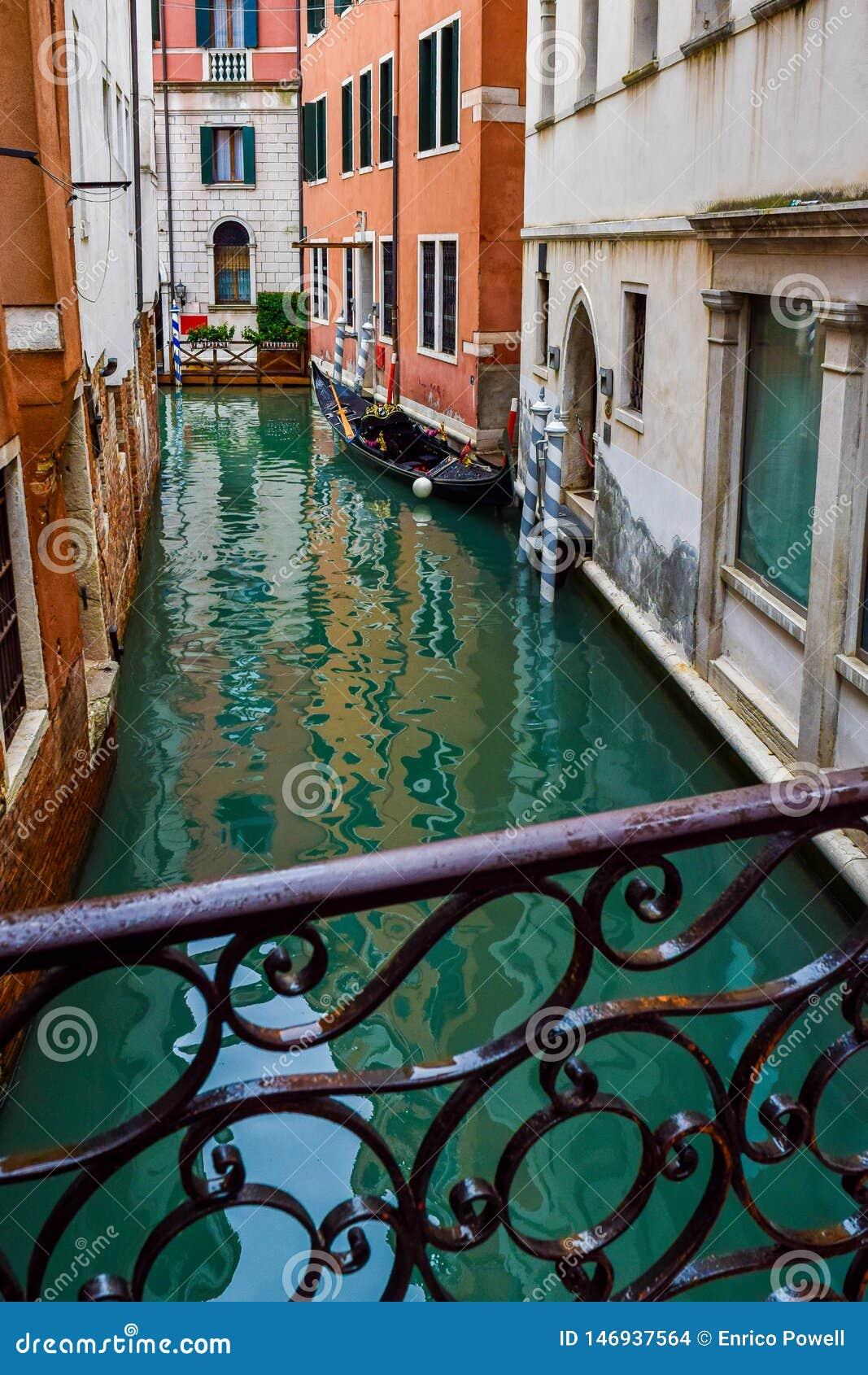 La vue de la gondole en bois vide s est accouplée garé amarré près des bâtiments sur le canal étroit de l eau du pont à Venise, I